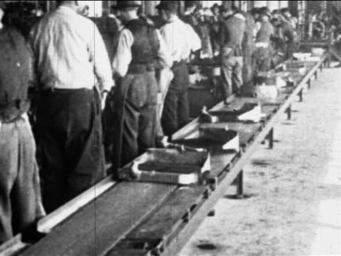 b/w 1910s rear view men facing away from moving conveyor belt / ford factory, highland park, mi - ford motor company stock videos and b-roll footage