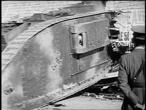 b/w 1910s rear view men in military uniforms watching large tank crash through bldg / world war i - kampfpanzer stock-videos und b-roll-filmmaterial
