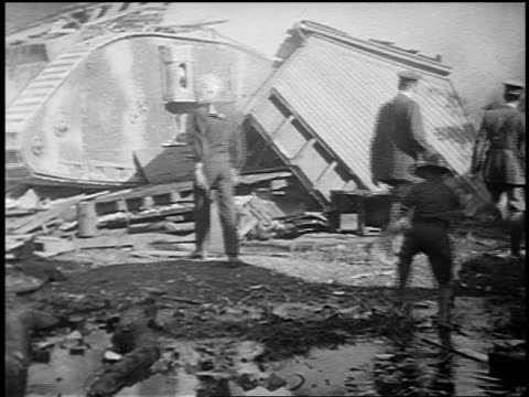 1910s rear view men in military uniforms watching large tank crash through house / world war i - kampfpanzer stock-videos und b-roll-filmmaterial