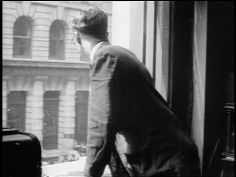 B/W 1910s REAR VIEW Wall Street broker leaning out of window + signaling / NYC