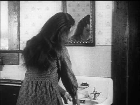B/W 1910s REAR VIEW woman with long hair washing face in sink + looking in mirror / documentary