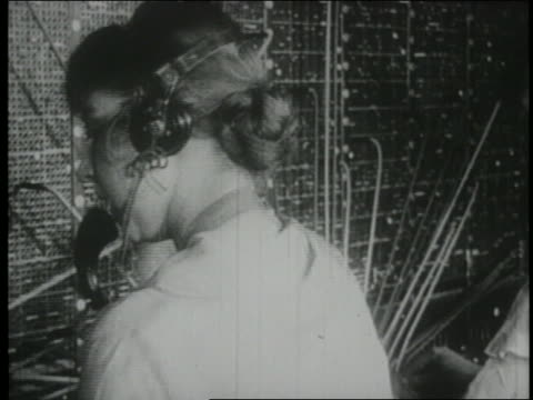 b/w 1910s rearview female telephone operator at switchboard - 電話交換機点の映像素材/bロール