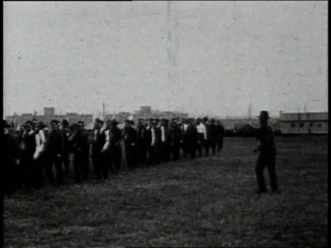 1910s recruits in shirtsleeves learning to march in formation and carry rifles / united states - military recruit stock-videos und b-roll-filmmaterial