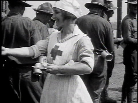 1910s red cross girl handing papers to line of soldiers / michigan, united states - red cross stock videos & royalty-free footage