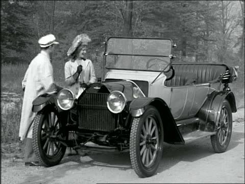 b/w 1910s reenactment woman surprised at man polishing convertible chevrolet; they get into car - chevrolet stock videos & royalty-free footage