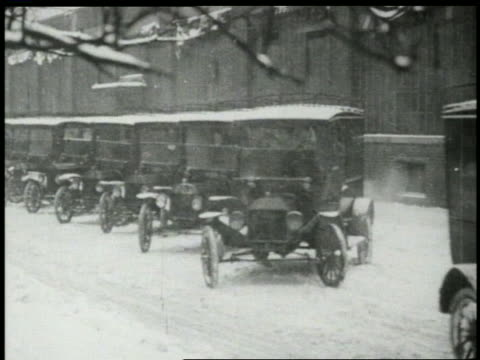 B/W 1910s row of cars/trucks pulling out of snowy parking lot