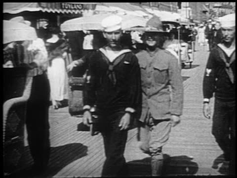 stockvideo's en b-roll-footage met b/w 1910s sailors + soldier walking towards camera on boardwalk / pushcarts in background / atlantic city - 1915
