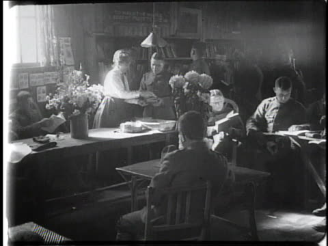 1910s ws soldiers reading and checking out books in a small library / france - 図書館員点の映像素材/bロール