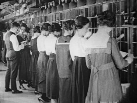 b/w 1910s standing female postal workers file mail into slots / documentary - postamt stock-videos und b-roll-filmmaterial