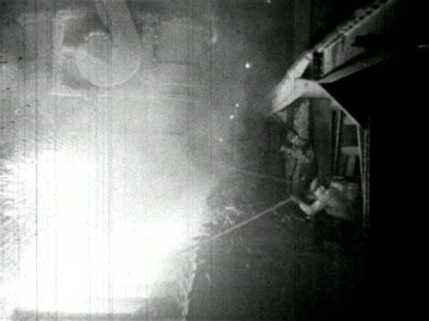 vídeos de stock e filmes b-roll de b/w 1910s steelworker pokes blazing furnace with pole / newsreel - fábrica de aço
