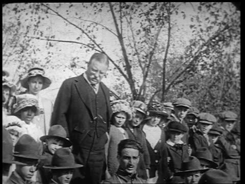 B/W 1910s Theodore Roosevelt standing with children saluting / World War I / newsreel