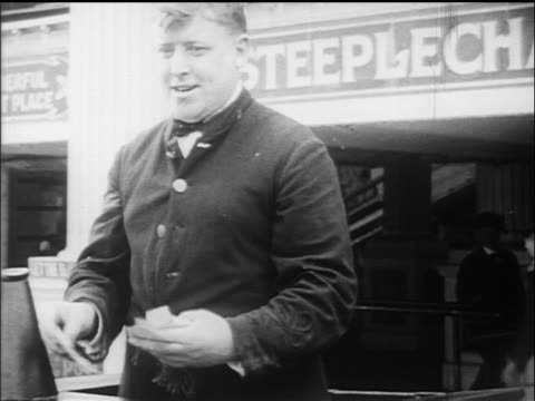 b/w 1910s ticket chopper taking tickets for steeplechase ride / coney island, nyc / documentary - coney island brooklyn stock videos & royalty-free footage