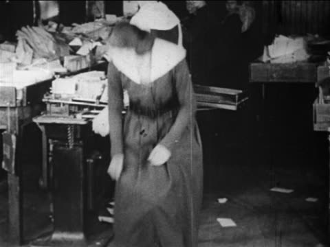 b/w 1910s tilt down female postal worker picks up pile of mail from floor / documentary - postal worker stock videos & royalty-free footage
