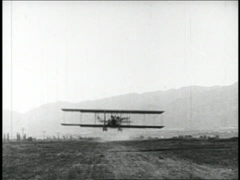 b/w 1910s tilt up 2 people in biplane flying over camera / feature - 1910 stock-videos und b-roll-filmmaterial