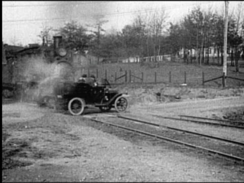 b/w 1910s train crashing into car on tracks / car smashed into pieces - due oggetti video stock e b–roll