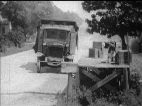 B/W 1910s truck driving up to platform with boxes + calf on it / documentary