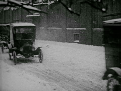 trucks ws ford panel trucks pulling out of line one by one driving on snow covered ground ha ws delivery truck in city la ws man unloading milk... - anno 1910 video stock e b–roll