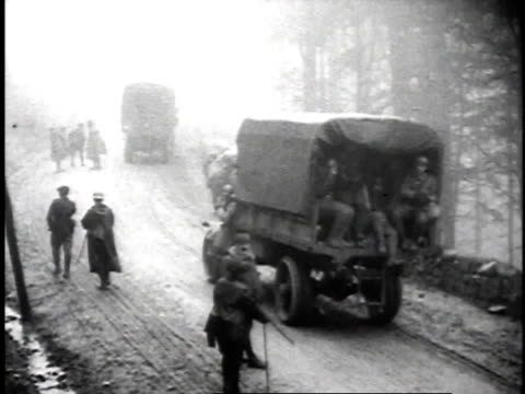 1910s MS Trucks passing pedestrians on road / France