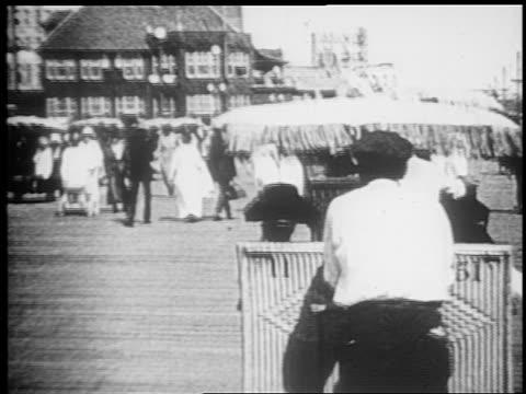 vidéos et rushes de b/w 1910s walking point of view behind man pushing pushcart on boardwalk / atlantic city - allée couverte de planches