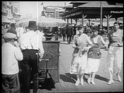 stockvideo's en b-roll-footage met b/w 1910s walking point of view behind people being pushed in pushcart on boardwalk / atlantic city - gemengde leeftijdscategorie