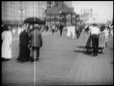 b/w 1910s walking point of view on crowded boardwalk with pushcarts / atlantic city, new jersey - boardwalk stock videos & royalty-free footage