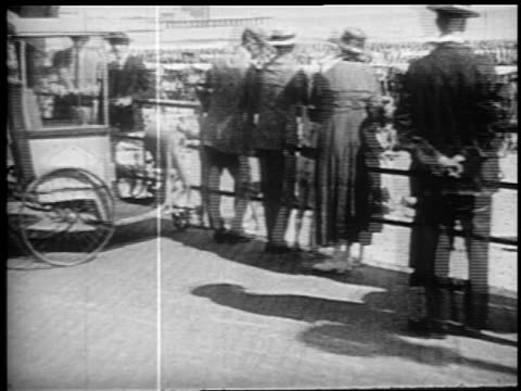 b/w 1910s walking point of view past people at railing of boardwalk / man with camera atlantic city, nj - 撮影機材点の映像素材/bロール