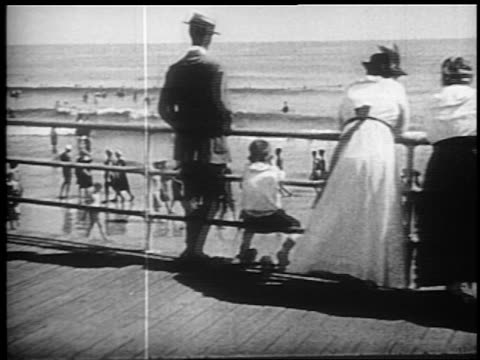 b/w 1910s walking point of view people looking over railing of boardwalk to beach + ocean / atlantic city, nj - punto di vista di un passante video stock e b–roll