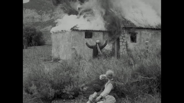 1910s while their house is set ablaze by turkish invaders, peasant woman (blanche sweet) and her young brother cower in the brush - hiding stock-videos und b-roll-filmmaterial