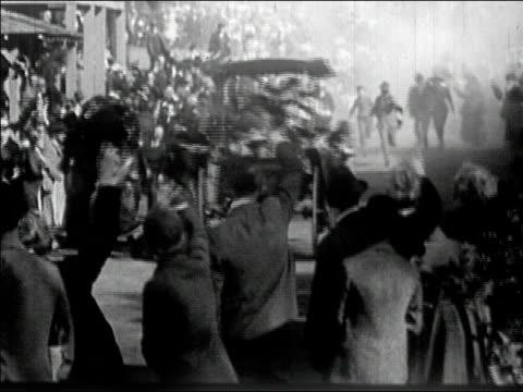 1910s  Wide shot crowd waves as car drives through street/ AUDIO