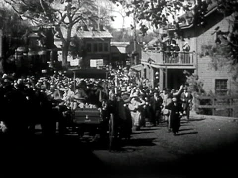 1910s wide shot crowd waving and chasing car down street/ audio - 1940~1949年点の映像素材/bロール