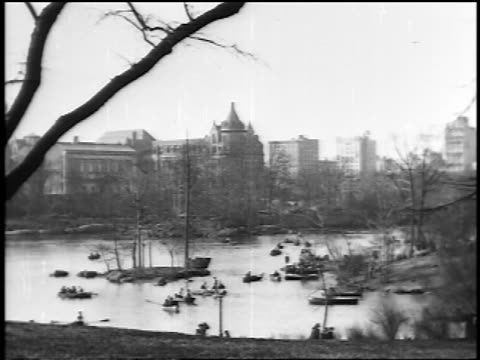 b/w 1910s wide shot people boating on lake in central park / buildings in background / nyc / newsreel - new york city 1910s stock videos & royalty-free footage