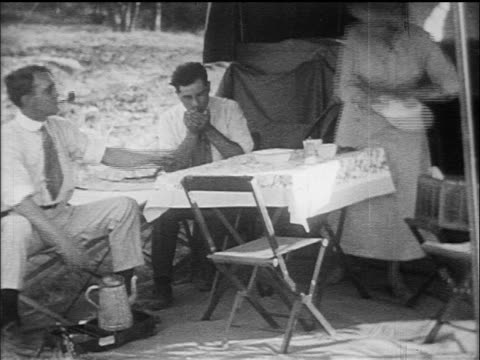 b/w 1910s woman + 2 men eating picnic on table under tent outdoors / documentary - smoking activity stock videos & royalty-free footage