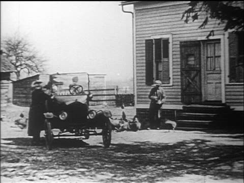 b/w 1910s woman getting into model t car with children + drives off from farmhouse / documentary - フォード・t型モデル点の映像素材/bロール