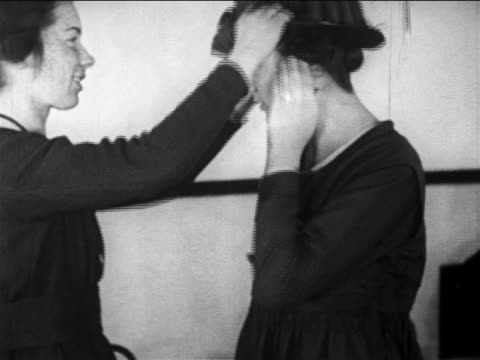 b/w 1910s woman helping other woman put on hat / documentary - 1910 stock videos & royalty-free footage