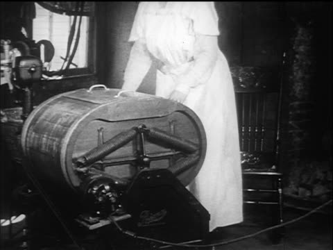b/w 1910s woman in rocking chair turning off early washing machine + rings out clothes / documentary - 専業主婦点の映像素材/bロール