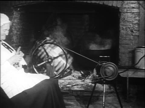 b/w 1910s woman sitting by fire knitting next to electric butter churn / documentary - rocking chair stock videos & royalty-free footage