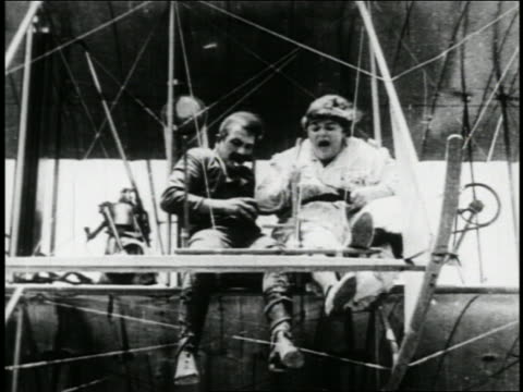 b/w 1910s woman (fatty arbuckle) trying to stop man (edgar kennedy) in biplane from dropping bombs - fatty arbuckle stock videos and b-roll footage