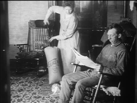 b/w 1910s woman vacuuming carpet as man reads newspaper in rocking chair / documentary - stereotypical housewife stock videos & royalty-free footage