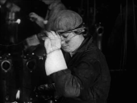 vídeos de stock e filmes b-roll de b/w 1910s woman working in defense factory removes goggles + smiles for camera / documentary - óculos de proteção
