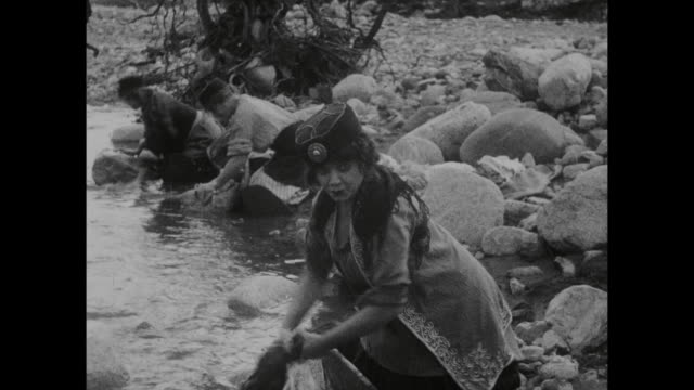 1910s  woman's (blanche sweet) jealousy starts to show when man's (house peters) inability to wash clothes in a stream attract attention of other women - 1915年点の映像素材/bロール
