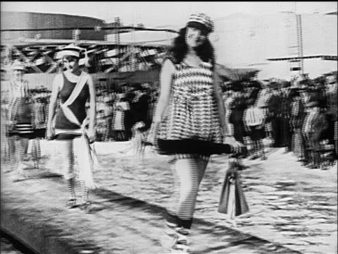 B/W 1910s women modeling swimsuits on walkway