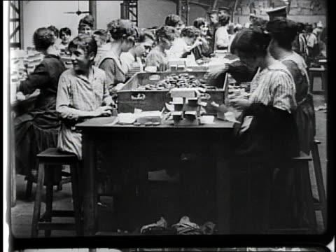 vidéos et rushes de 1910s workers at tables packing boxes / france - 1910