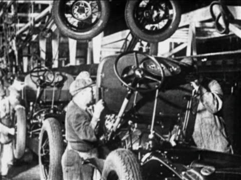 stockvideo's en b-roll-footage met b/w 1910s workers lower dashboards onto cars on assembly line / ford factory, highland park, mi - assemblagelijn