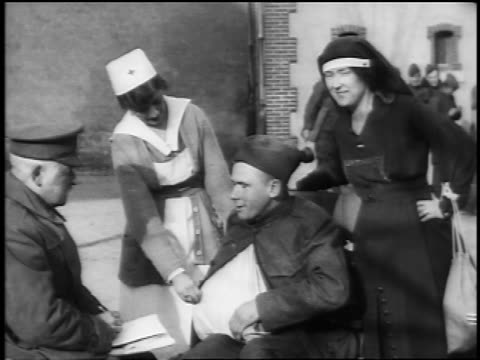 B/W 1910s wounded soldier sitting talking to officer as nurses stand by him / documentary