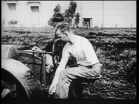 b/w 1910s wounded world war i veteran with one arm climbing into tractor as soldier assists him / news - tractor stock videos & royalty-free footage