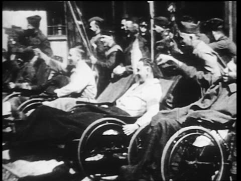 B/W 1910s wounded World War I veterans cheering / some in wheelchairs / newsreel