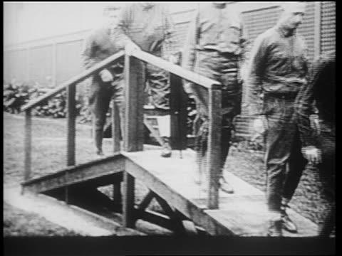B/W 1910s wounded World War I veterans crossing footbridge / newsreel