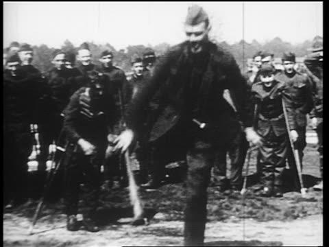 B/W 1910s wounded World War I veterans in uniform playing baseball / onelegged man at bat / news