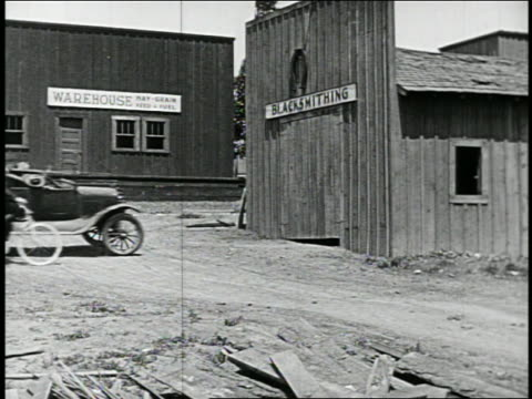 b/w 1910s/20s car crashing into blacksmith shop as man rides bicycle past building / feature - non urban scene stock videos & royalty-free footage