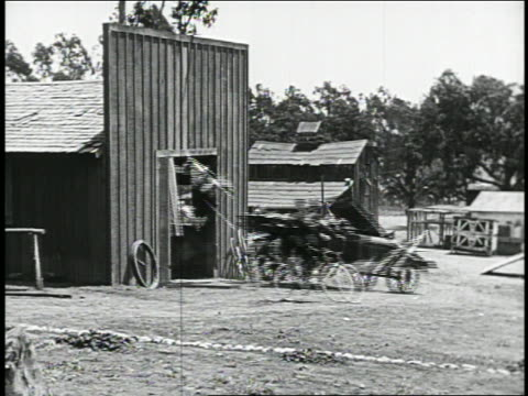b/w 1910s/20s car crashing out of barn with man riding bicycle beside it / feature - 1910 stock-videos und b-roll-filmmaterial